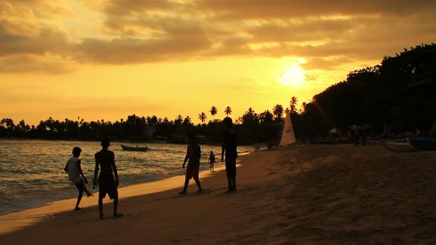 people on a beach at sunset, unawatuna beach, sri lanka