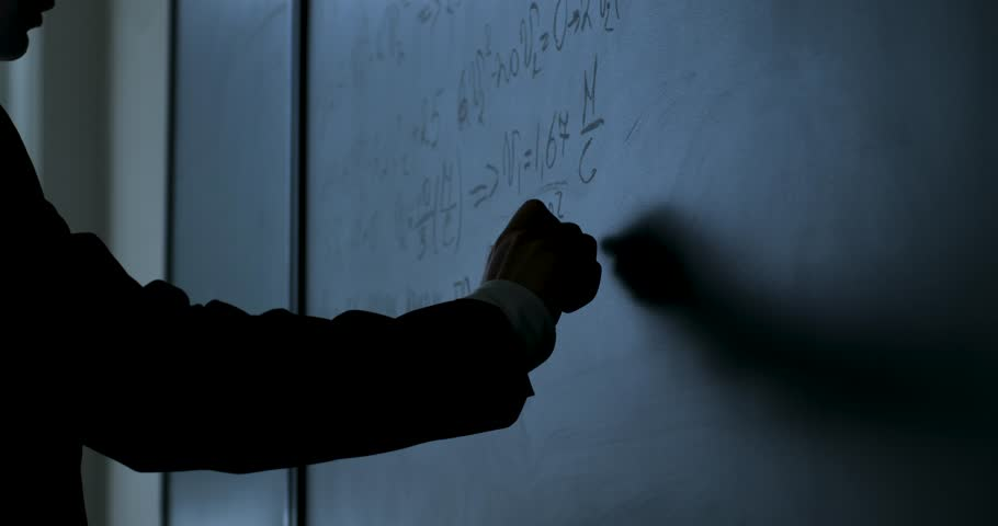 Scientist writing formulas on chalkboard. Hand with chalk wrote physics formulas on black chalkboard closeup
