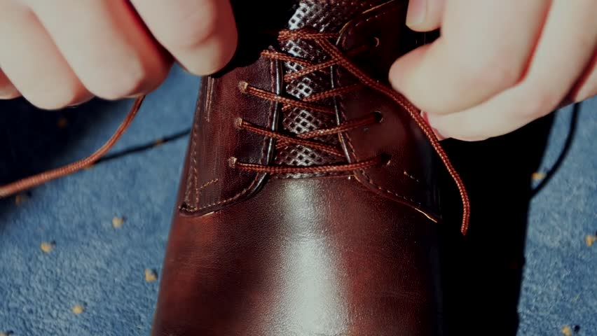 Man tying patent leather shoes. / Man tying patent leather shoes formal and festive dressing. Slow motion. Close up
