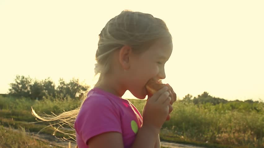 Cute kid girl eating sweet donut outdoor in the park on sunny warm day. Close Up Of Girl Eating Iced Donut.   Shutterstock HD Video #29053075