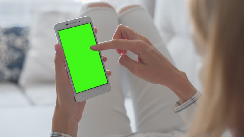 Young Woman in white jeans laying on couch uses SmartPhone with pre-keyed green screen. Few types of gestures - scrolling up and down, tapping, zoom in and out.  | Shutterstock HD Video #29065288