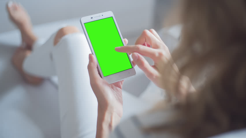Young Woman in white jeans sitting on couch uses SmartPhone with pre-keyed green screen. Few types of gestures - scrolling up and down, tapping, zoom in and out.  | Shutterstock HD Video #29065318