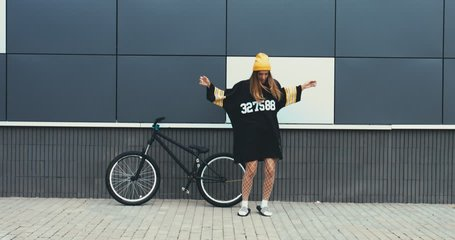 Young stylish Caucasian female dancing near a bicycle against grey wall background. 4K UHD RAW edited footage