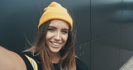 CU Outdoor portrait of young attractive female in stylish outfit making a selfie. Phone camera POV. 4K UHD RAW edited footage