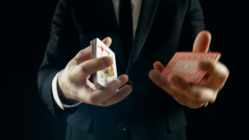 Close-up of a Magician's Hands Performing Card Trick. Throwing and Catching Cards Deck in the Air. Background is Black. Slow Motion. Shot on RED EPIC-W 8K Helium Cinema Camera.