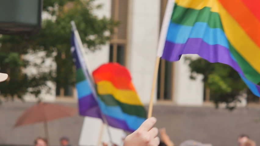 Two rainbow flags waves as people walk march by with protest signs during gay pride GLBT LGBT festival. Slow motion. Symbol of Gay lesbian transgender queer rights, activism love equality and freedom