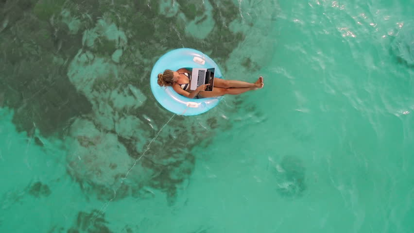 Aerial drone quad copter footage of woman using laptop computer, concept of tourist woman floating on lilo inflatable and working on laptop computer in tropical exotic ocean. Remote working anywhere.