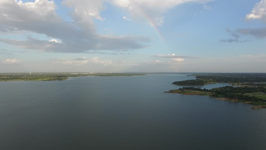Aerial flight over Grapevine Lake with rainbow in the clouds.   Shutterstock HD Video #29118391