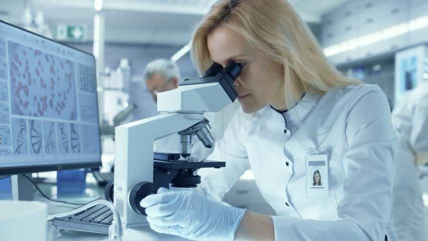 Female Research Scientist Looks at Biological Samples Under Microscope. She and Her Colleagues Work in a Big Modern Laboratory/ Medical Center. Shot on RED EPIC-W 8K Helium Cinema Camera.