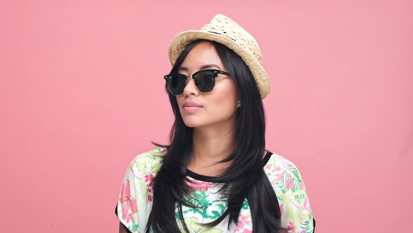 Young happy asian lady wearing hat and sunglasses waving to friends over pink background   Shutterstock HD Video #29141680