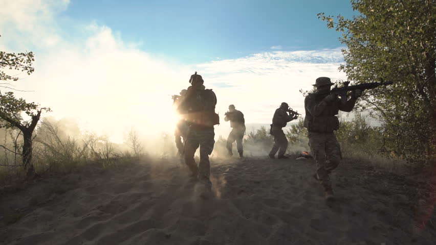 Silhouettes of soldiers walking on battlefield and aiming with guns through the smoke