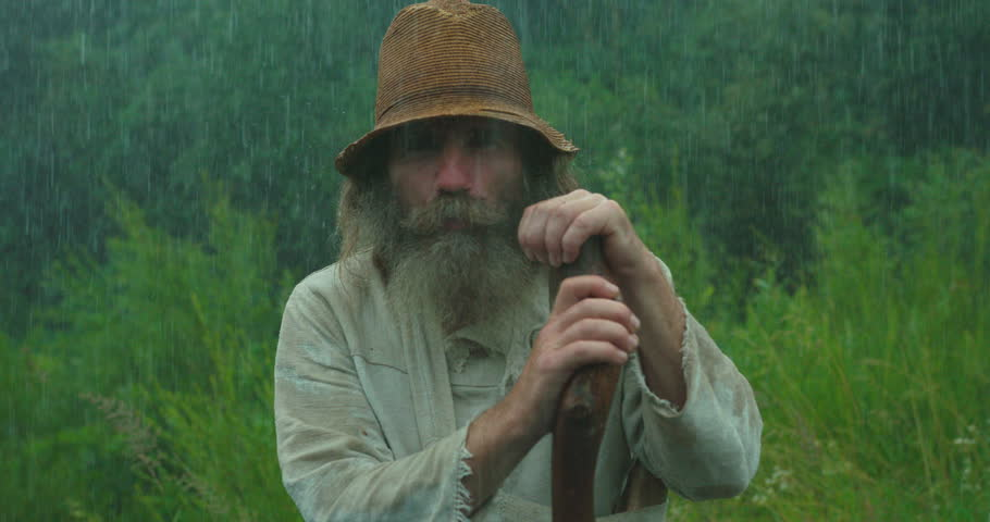 Close-up portrait of the old man with long beard, in old clothes is chewing while leaning on the cane in the rain.