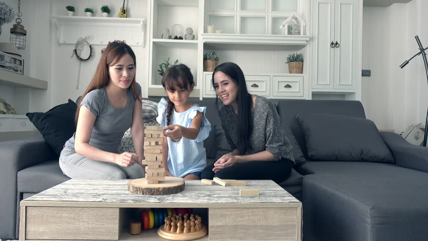 Young girl playing game with mother and asian nanny in living room. Beautiful white child playing block with her mother and pretty young asian nanny at home in the afternoon. | Shutterstock HD Video #29164168