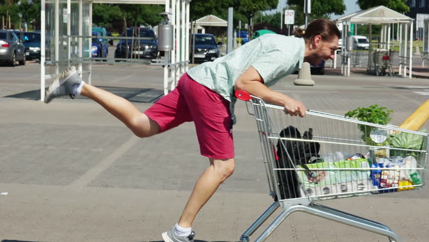 A young man is riding a trolley in a parking lot near a supermarket. The basket is full of products. Fun and good mood. Merry shopping. Dad buys food | Shutterstock HD Video #29166478