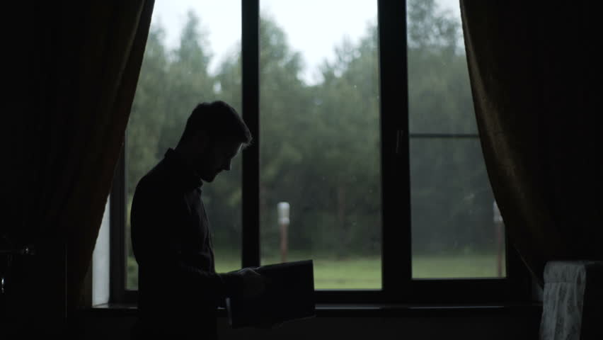 Silhouette of the man walking near window and looks at documents #29168212