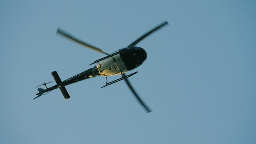 Shaky amateur witness footage tracking police helicopter flying over Los Angeles neighborhood. 4K UHD.