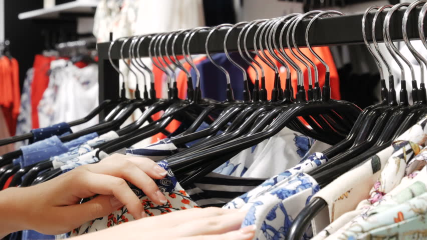 Woman in the shop looks through the shirts, which are hanging on the racks. hands run across a rack of clothes, browsing in a boutique. Head-on view with rack focus. | Shutterstock HD Video #29202409