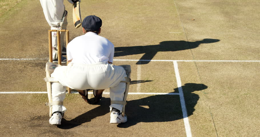Bowler delivering ball during match on cricket field