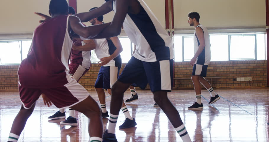 Determined diverse basketball players playing in the court