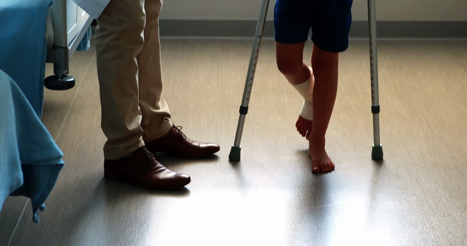 Male doctor assisting injured boy to walk with crutches in hospital