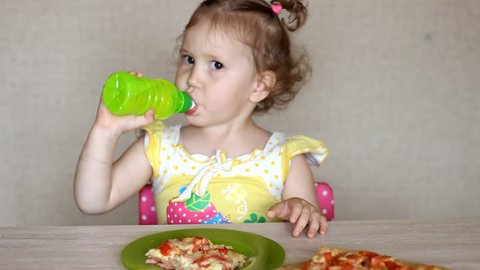 The child eats pizza and drinks lemonade. Cafe and fast food.