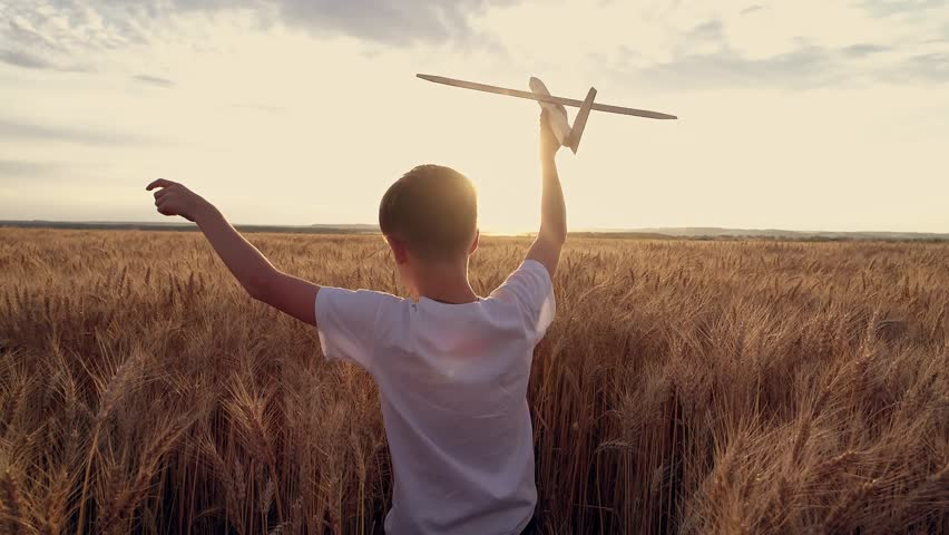 Happy child runs with a toy airplane on a sunset background over a wheat field. Boy dreams of becoming an airplane pilot children dreams of an airplane pilot