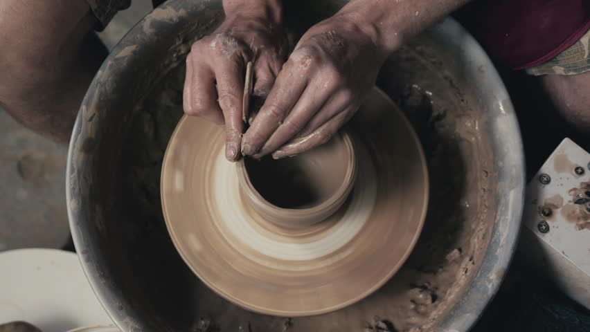 Potter shapes the clay product with pottery tools on the potter's wheel, top view, toned cinematic, craft factory authentic