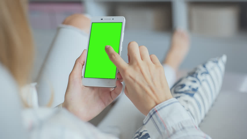 Young Woman in white jeans laying on couch uses SmartPhone with pre-keyed green screen. Few types of gestures - scrolling up and down, tapping, zoom in and out. Perfect for screen compositing | Shutterstock HD Video #29241526