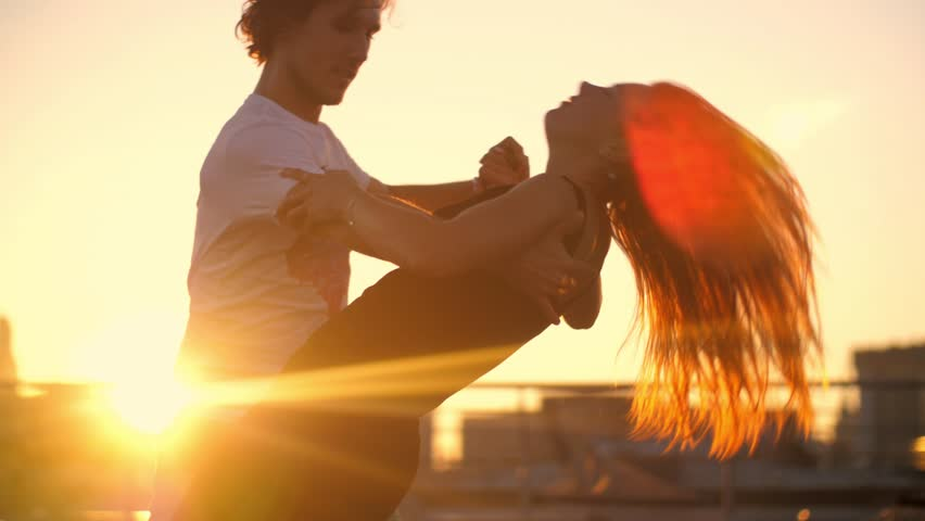 Young couple dancing zouk dance on rooftop with city skyline and sunset sun in background. Slow motion, 4K UHD