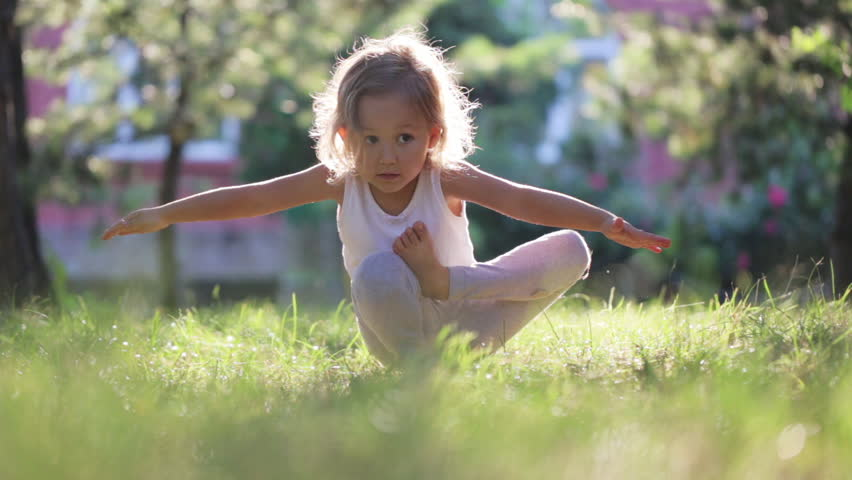 Little cute baby girl doing yoga exercise on the grass at beautiful sun light in green summer park.