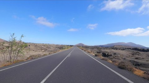 LANZAROTE, SPAIN - CIRCA JUNE, 2017: POV Driving in the desert with blue sky on the island of Lanzarote, Canary Islands