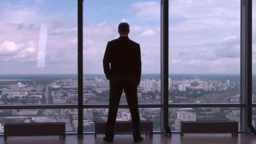 Full length back view of successful businessman in suit standing in office with hands on waist, CEO. Businessman from the back in front of a city view on the window