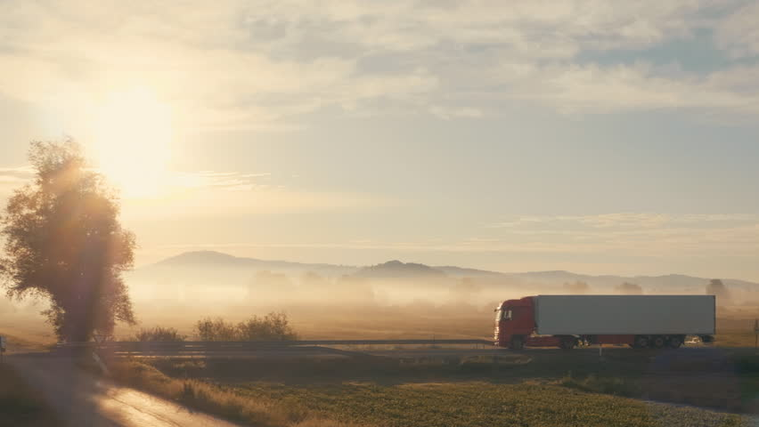 Side tracking aerial shot of a truck on the road in a beautiful early morning scenery.