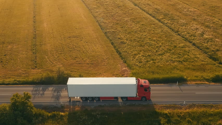 Aerial side shot of a truck on the road in beautiful countryside in the sunset light.