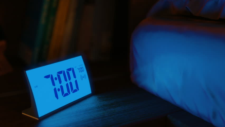 Digital alarm clock waking up at 7 AM. Close-up view. The clock screen is switching on for two seconds, then switching off for one second and go on. 3D rendering animation.