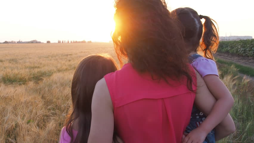 Mom and children watching the sunset. Mom hugs the children at sunset. #29318479