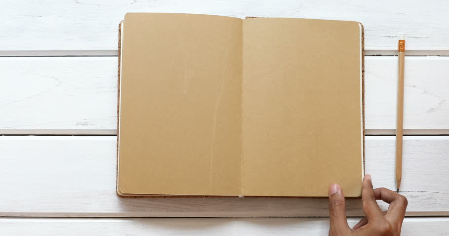 A male hand open diary brown paper 6 page then close  on the white wooden desk, top view and overhead shot use for blank template book mock up to add any text content, 4K Dci resolution