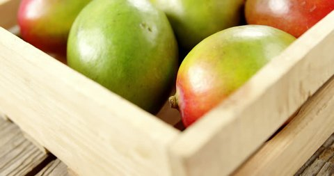 Close-up of red shiny mangoes in wooden crate