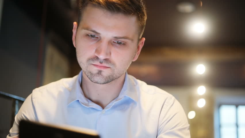 Handsome young man using tablet smiling sitting inside emotional face expression interest surprised nodding head agreement agreeing smiling internet searching looking screen lighted face brunette | Shutterstock HD Video #29344246