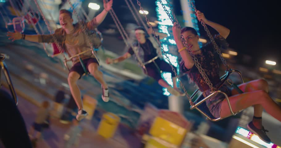 Happy teenage best friends riding the chairoplane carousel and having fun at the funfair #29344936