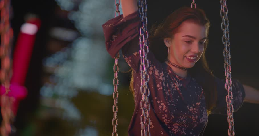 Group of hipster teenage friends having fun on carousel swings at amusement park at night Royalty-Free Stock Footage #29344951