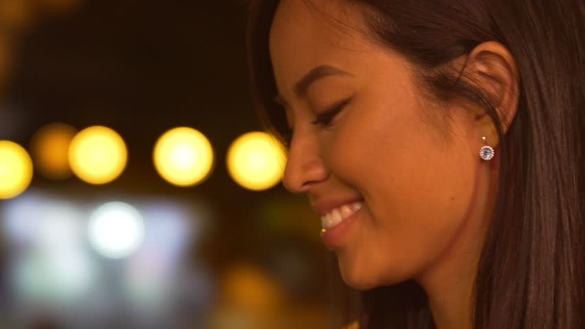 Close up of a beautiful asian woman using mobile phone and holding beer bottle while standing on a street at night #29350852