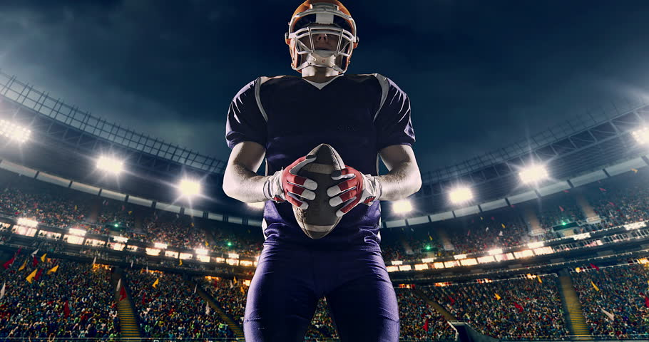 American football player is cheering on a professional sports stadium. He is wearing unbranded sport clothes. The stadium is made in 3D with animated crowd.