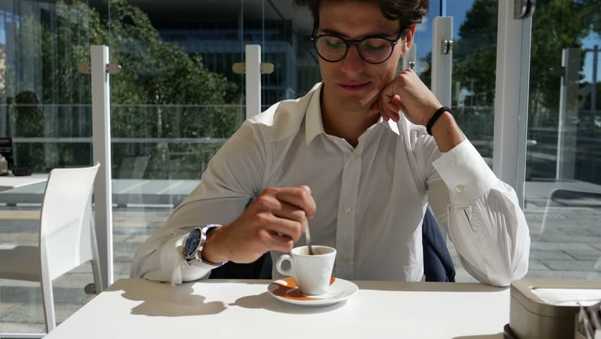 Young man in glasses and white shirt posing at table and drinking coffee in outside cafe. | Shutterstock HD Video #29353705