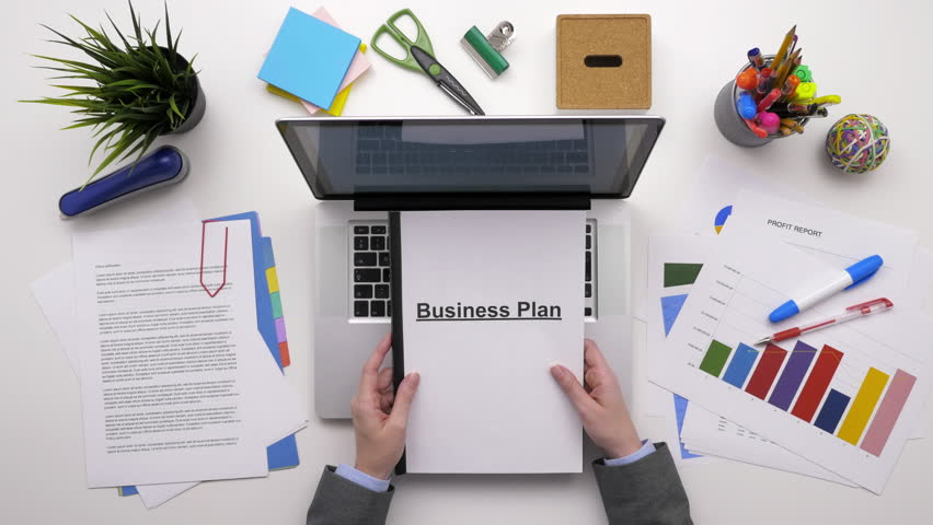 Top View Overhead Footage Of Businesswoman With Business Plan Using Laptop