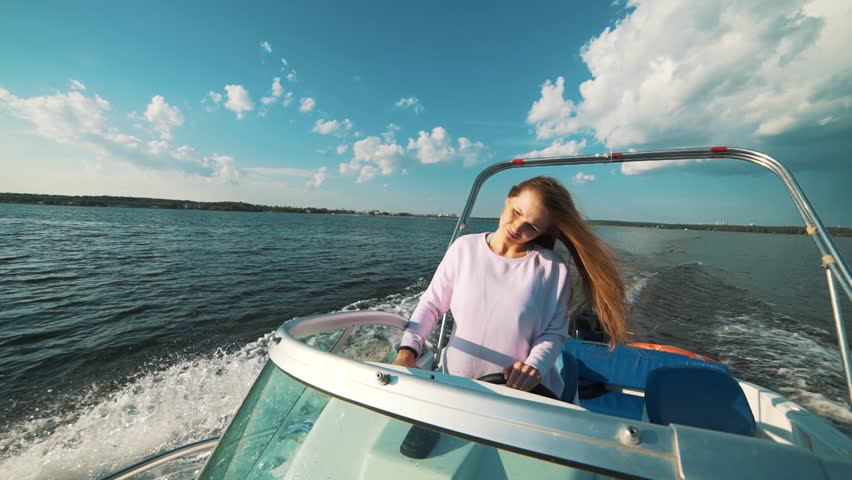 Summer vacation - young girl driving a motor boat | Shutterstock HD Video #29360128