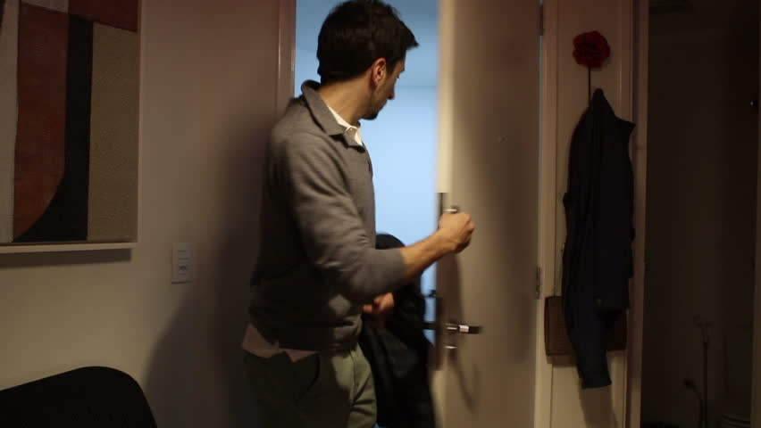 Person enters home through front door. Bachelor enters home,  turns on the lights, and puts overcoat on holder #29371678