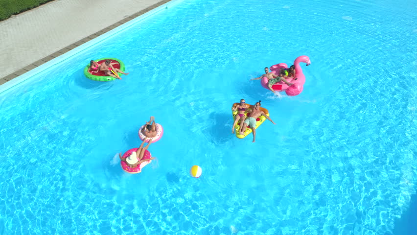 AERIAL: Cheerful friends having fun on colorful floaties at summer pool party. Playful guys and girls splashing water and taking selfies on inflatable pizza, doughnut, flamingo and watermelon floats | Shutterstock HD Video #29373550