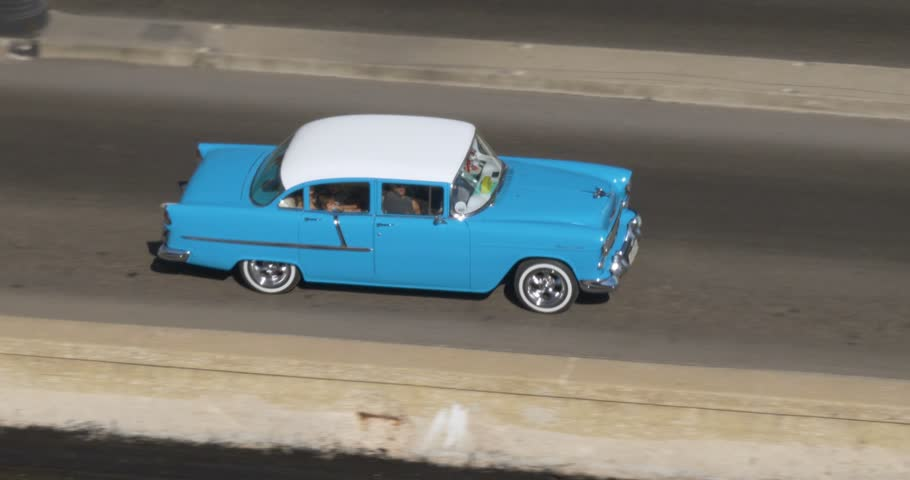 A high angle aerial view of colorful classic cars traveling on the streets of Havana, Cuba.
