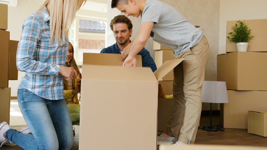 Close up shot of young happy family opening box with their things in the new living room, talking and smiling. #29380357